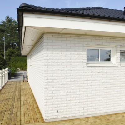 Hus med en fasad med rundhugget mexitegel.